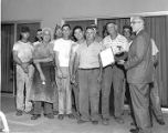 [Group of workers being presented with an award]